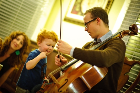 Ben Sollee captured by photographer Kory Johnson in a very special moment at a house concert in 2011.